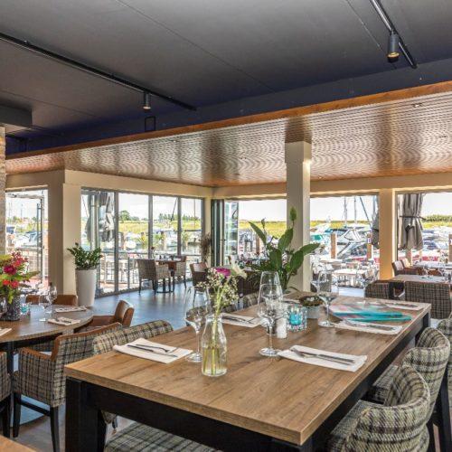 Inrichting van Brasserie Blush. Doorkijk van binnen naar het terras met uitzicht op de luxe jachthaven van Kamperland.