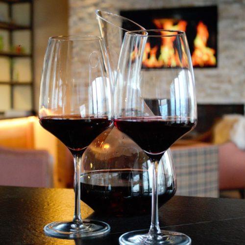 2 glazen rode wijn met een karaf voor een brandende open haard